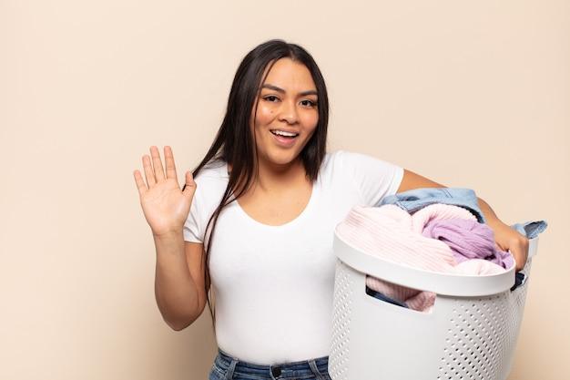 Jonge latijnse vrouw die gelukkig en opgewekt glimlacht, hand zwaait, u verwelkomt en begroet