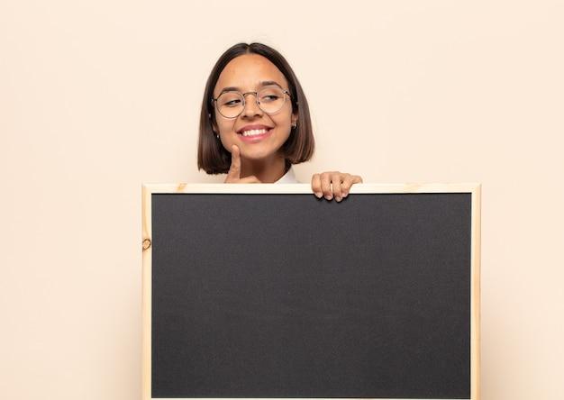 Jonge latijnse vrouw die gelukkig glimlacht en dagdroomt of twijfelt, op zoek naar de kant