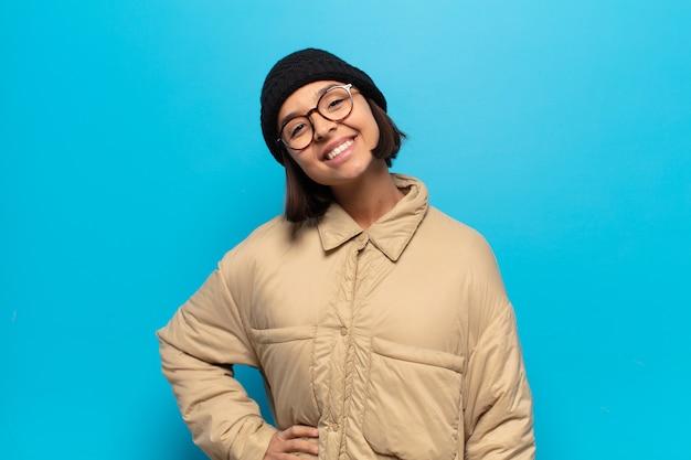 Jonge latijnse vrouw die gelukkig glimlacht met een hand op heup en zelfverzekerde, positieve, trotse en vriendelijke houding