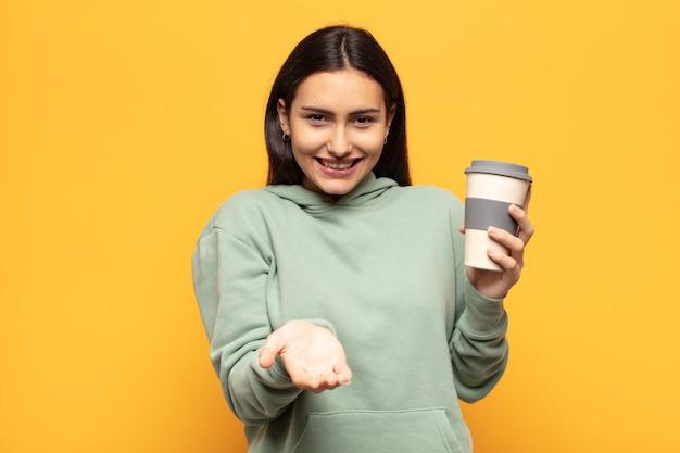 Jonge latijnse vrouw die gelukkig glimlacht met een vriendelijke, zelfverzekerde, positieve blik, een object of concept aanbiedt en toont