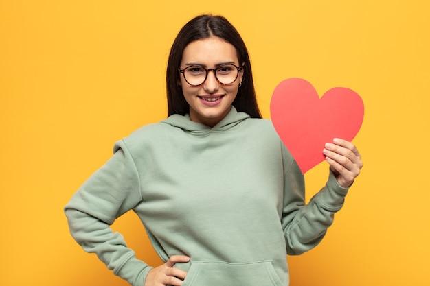 Jonge latijnse vrouw die gelukkig lacht met een hand op de heup en een zelfverzekerde, positieve, trotse en vriendelijke houding
