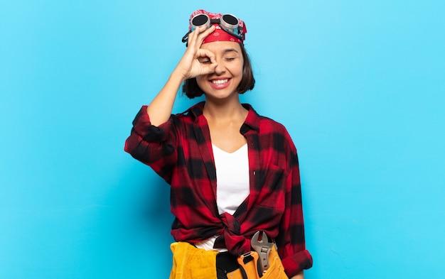 Jonge latijnse vrouw die gelukkig met grappig gezicht glimlacht, een grapje maakt en door kijkgaatje kijkt, geheimen bespioneert