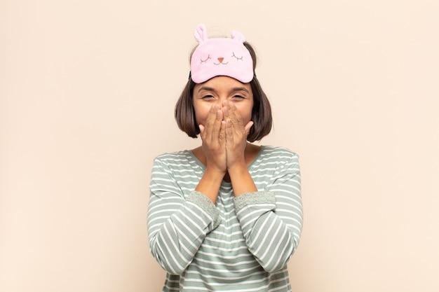 Jonge latijnse vrouw die gelukkig, vrolijk, gelukkig en verrast kijkt en de mond bedekt met beide handen