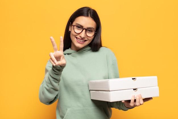 Jonge latijnse vrouw die gelukkig, zorgeloos en positief glimlacht en kijkt, met één hand overwinning of vrede gebaart