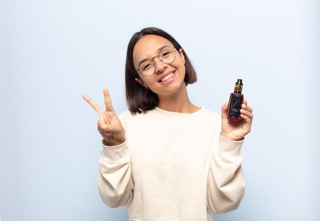 Jonge latijnse vrouw die gelukkig, zorgeloos en positief glimlacht en kijkt, overwinning of vrede met één hand gebaart