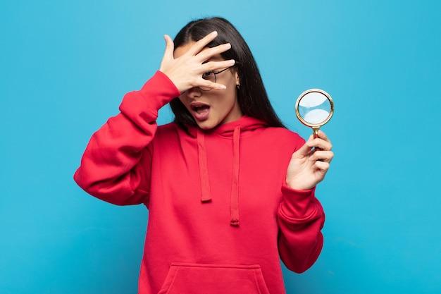 Jonge latijnse vrouw die geschokt, bang of doodsbang kijkt, gezicht bedekt met hand en tussen vingers gluurt