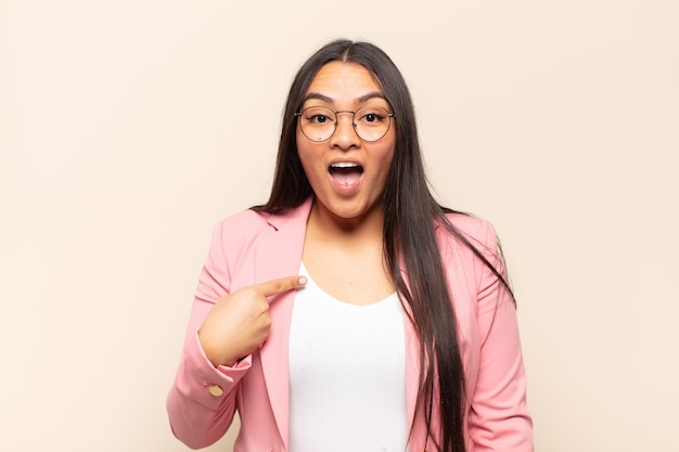 Jonge latijnse vrouw die geschokt en verrast kijkt met wijd open mond, wijzend naar zichzelf