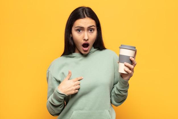 Jonge latijnse vrouw die geschokt en verrast met wijd open mond kijkt