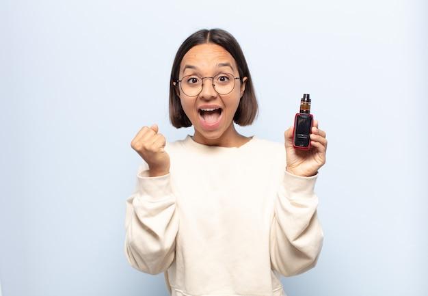 Jonge latijnse vrouw die geschokt, opgewonden en gelukkig voelt, lacht en succes viert, zeggend wow!