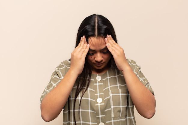 Jonge latijnse vrouw die gestrest en gefrustreerd kijkt, onder druk werkt met hoofdpijn en last heeft van problemen