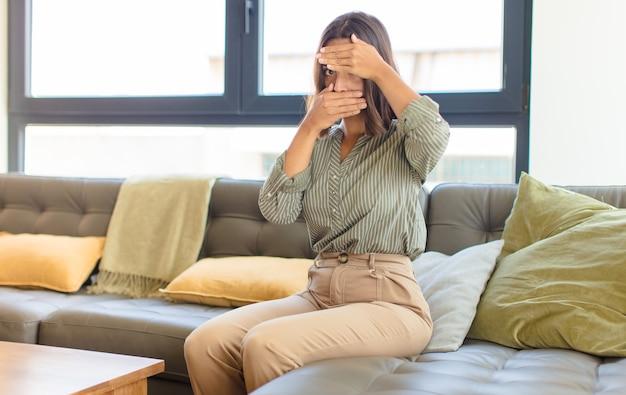 Jonge latijnse vrouw die gezicht behandelt met beide handen die nee zeggen tegen de camera! afbeeldingen weigeren of foto's verbieden