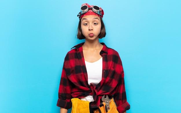 Jonge latijnse vrouw die goofy en grappig kijkt met een dwaze schele uitdrukking, een grapje maakt en voor de gek houdt