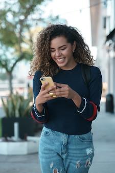 Jonge latijnse vrouw die haar mobiele telefoon gebruikt terwijl ze buiten op straat loopt. stedelijk begrip.