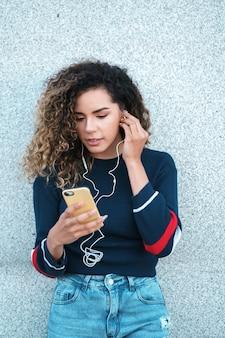 Jonge latijnse vrouw die haar mobiele telefoon gebruikt terwijl ze buiten op straat staat. stedelijk begrip.