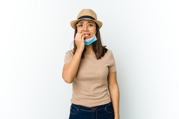 Jonge latijnse vrouw die hoed en masker draagt om tegen covid te beschermen die op witte muur wordt geïsoleerd die vingernagels bijt, zenuwachtig en zeer angstig.