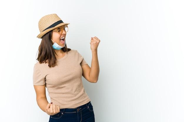 Jonge latijnse vrouw die hoed en masker draagt om tegen covid te beschermen die op witte muur wordt geïsoleerd die vuist opheft na een overwinning, winnaarconcept.