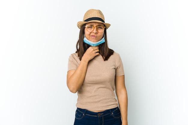 Jonge latijnse vrouw die hoed en masker draagt om tegen covid te beschermen die op witte muur wordt geïsoleerd, lijdt pijn in de keel als gevolg van een virus of infectie.