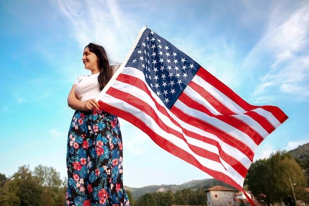 Jonge latijnse vrouw die lacht en amerikaanse vlag vasthoudt op een landelijke plaats