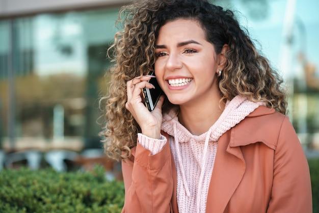 Jonge latijnse vrouw die lacht terwijl ze buiten op straat aan de telefoon praat. stedelijk begrip.