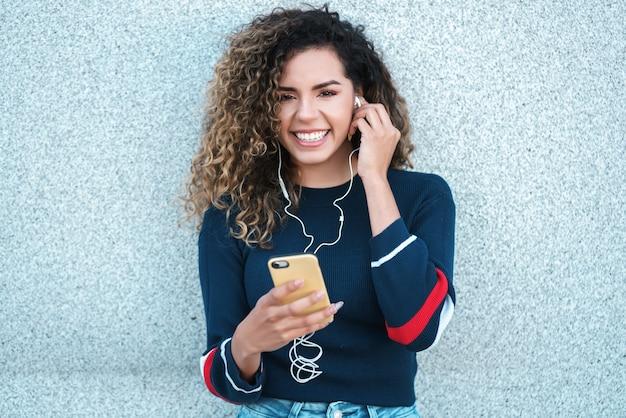 Jonge latijnse vrouw die lacht terwijl ze haar mobiele telefoon buiten op straat gebruikt. stedelijk begrip.