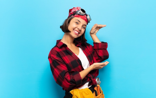 Jonge latijnse vrouw die lacht, zich gelukkig, positief en tevreden voelt, een object of concept vasthoudt of toont op kopieerruimte