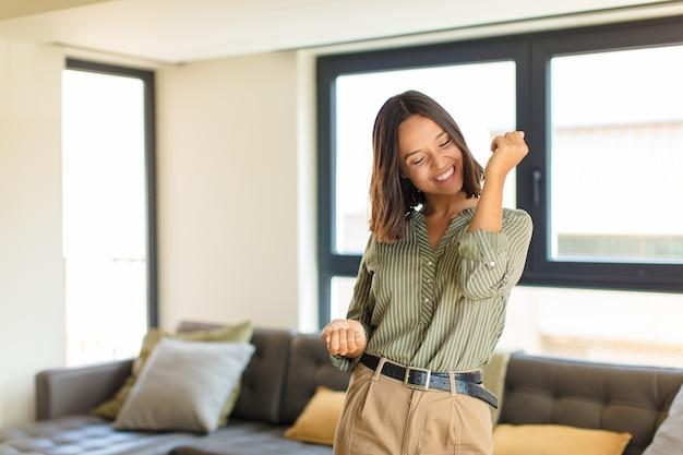 Jonge latijnse vrouw die lacht, zich zorgeloos, ontspannen en gelukkig voelt, danst en naar muziek luistert, plezier heeft op een feestje