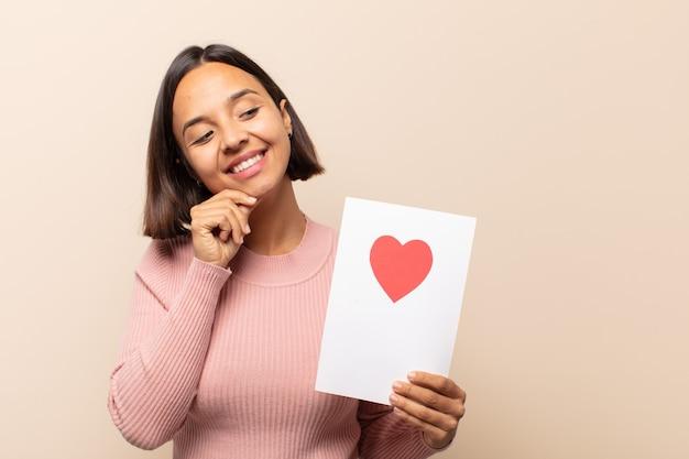 Jonge latijnse vrouw die met een gelukkige, zelfverzekerde uitdrukking glimlacht met hand op kin, zich afvraagt en naar de kant kijkt