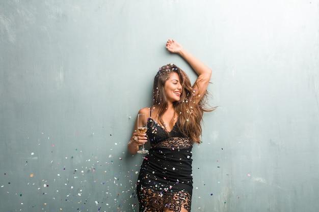 Jonge latijnse vrouw die nieuw jaar of een gebeurtenis viert. opgewonden en gelukkig, met een champagnefles en een beker.