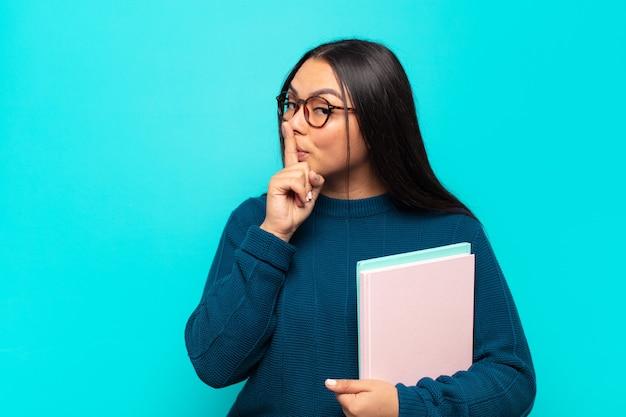 Jonge latijnse vrouw die om stilte en stilte vraagt, met vinger voor mond gebaart, shh zegt of een geheim houdt