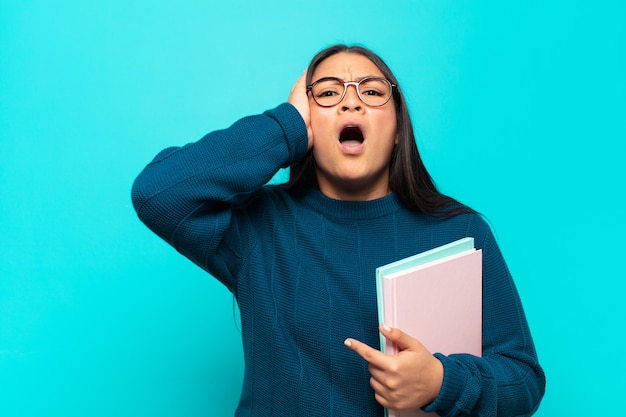 Jonge latijnse vrouw die onaangenaam geschokt, bang of bezorgd kijkt, met wijd open mond en beide oren bedekt met handen