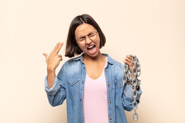 Jonge latijnse vrouw die ongelukkig en gestrest kijkt, zelfmoordgebaar die pistoolteken maakt met hand, die naar hoofd wijst