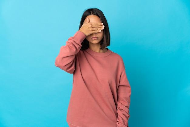 Jonge latijnse vrouw die op blauwe muur wordt geïsoleerd die ogen behandelt door handen. ik wil niets zien