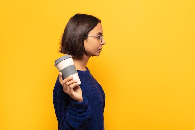 Jonge latijnse vrouw die op profielweergave ruimte vooruit wil kopiëren, denken, zich voorstellen of dagdromen