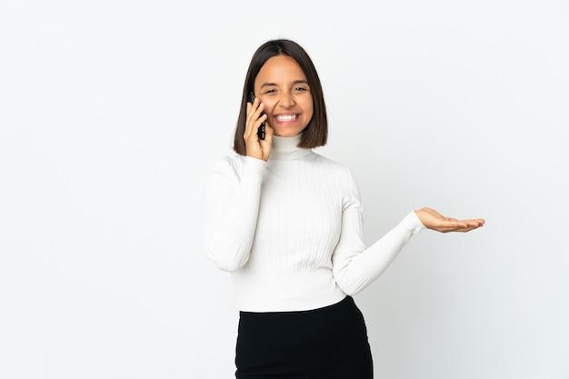 Jonge latijnse vrouw die op witte muur wordt geïsoleerd die een gesprek met de mobiele telefoon met iemand houdt