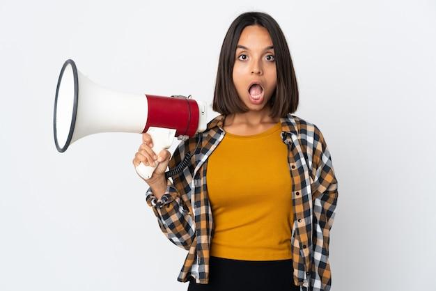 Jonge latijnse vrouw die op witte muur wordt geïsoleerd die een megafoon houdt en met verrassingsuitdrukking
