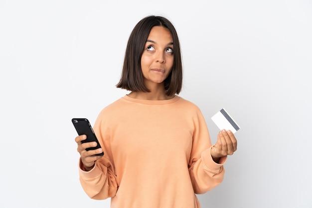 Jonge latijnse vrouw die op witte muur wordt geïsoleerd die met mobiel met een creditcard koopt terwijl het denken