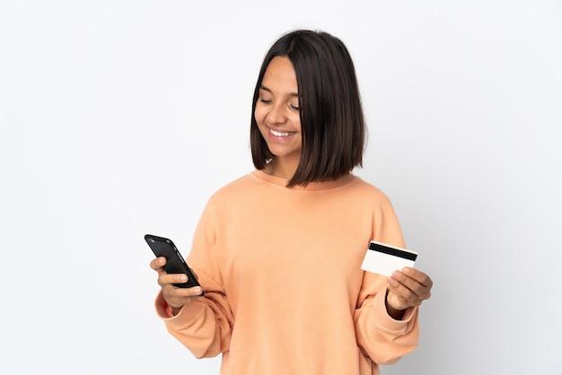 Jonge latijnse vrouw die op witte muur wordt geïsoleerd die met mobiel met een creditcard koopt