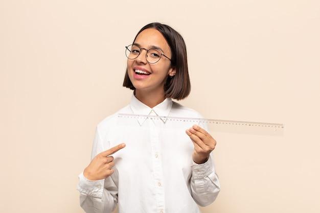 Jonge latijnse vrouw die opgewonden en verrast kijkt en naar de zijkant en naar boven wijst om ruimte te kopiëren copy