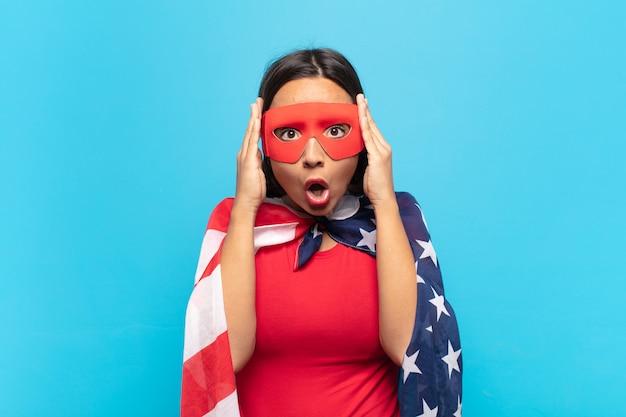 Jonge latijnse vrouw die opgewonden en verrast kijkt, met open mond met beide handen op het hoofd, voelt zich een gelukkige winnaar