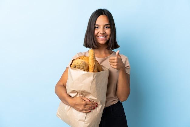 Jonge latijnse vrouw die sommige broden kopen die bij blauwe geven duimen op gebaar worden geïsoleerd