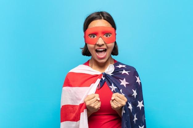 Jonge latijnse vrouw die triomfantelijk schreeuwt, lacht en zich blij en opgewonden voelt terwijl ze succes viert