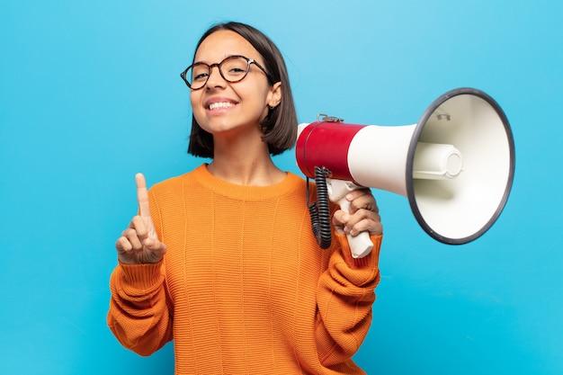 Jonge latijnse vrouw die trots en zelfverzekerd glimlacht en nummer één triomfantelijk poseert, voelt zich een leider