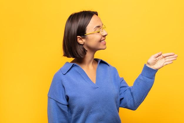 Jonge latijnse vrouw die, u begroet en een handschudt aanbiedt om een succesvolle overeenkomst, samenwerkingsconcept te sluiten