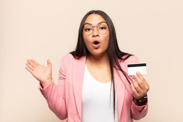 Jonge latijnse vrouw die verbaasd en geschokt kijkt, met open mond een voorwerp vasthoudt met een open hand op de zijkant