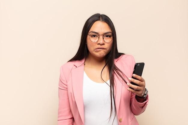 Jonge latijnse vrouw die verbaasd en verward kijkt, lip bijt met een nerveus gebaar, het antwoord op het probleem niet weet