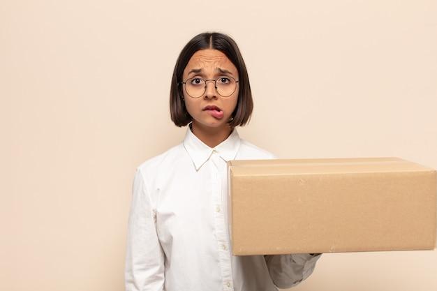 Jonge latijnse vrouw die verbaasd en verward kijkt, lip bijt met een nerveus gebaar, niet wetend het antwoord op het probleem