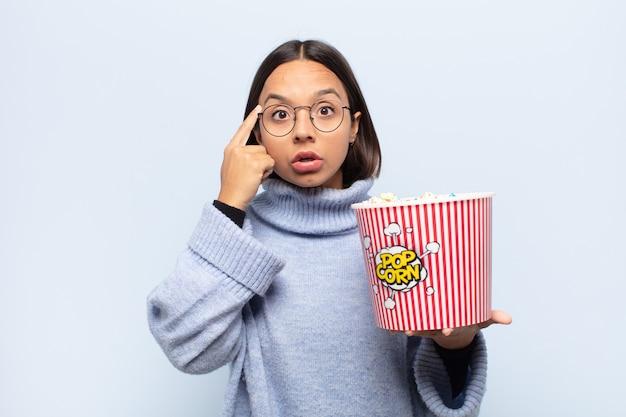 Jonge latijnse vrouw die verrast, met open mond, geschokt kijkt en een nieuwe gedachte, idee of concept realiseert