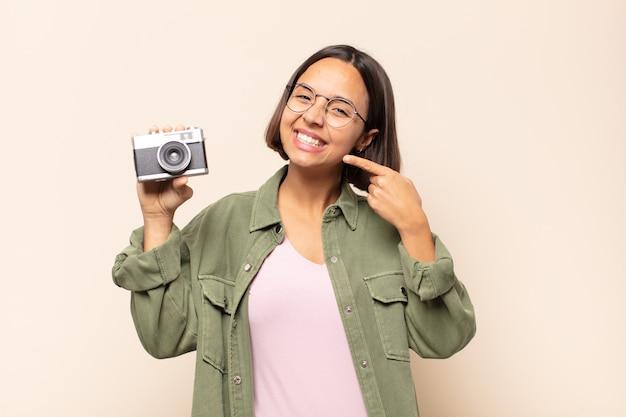 Jonge latijnse vrouw die vol vertrouwen glimlacht en wijst naar een brede glimlach, een positieve, ontspannen, tevreden houding