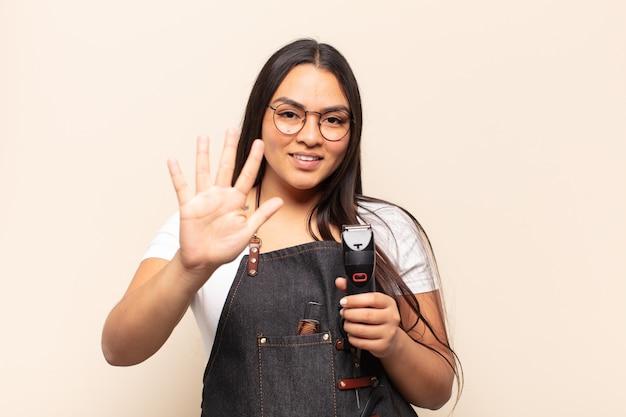 Jonge latijnse vrouw die vriendelijk glimlacht kijkt, nummer vijf of vijfde met vooruit hand toont, aftellend