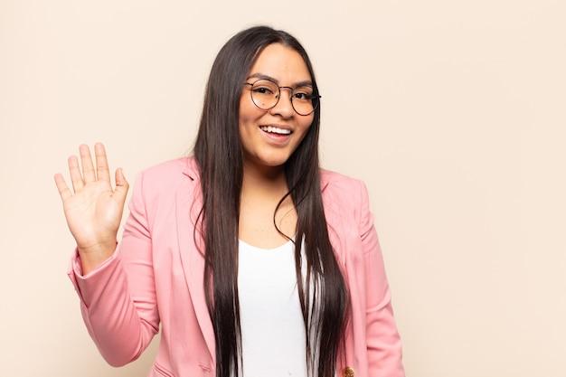 Jonge latijnse vrouw die vrolijk en opgewekt glimlacht, hand zwaait, je verwelkomt en begroet, of afscheid neemt